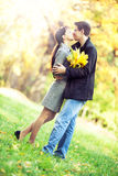 Couple kissing in the autumn park. Lovers spend sunny day in the autumn park, they kiss while holding a bouqet of autumn leaves Stock Photos