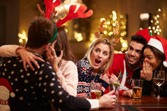 Couple Kissing In Bar As Friends Enjoy Christmas Drinks Royalty Free Stock Photography