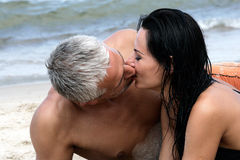 Couple kissing on the beach. Happy middle aged couple kissing on the beach, enjoying their summer holiday together Stock Image