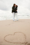 Couple kissing on beach. Young couple kissing on beach with love heart on sand in foreground Stock Photo