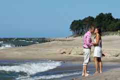 Couple kissing on beach. Romantic young couple kissing on sandy beach next to breaking waves Stock Images