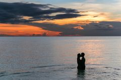 Couple kissing on the beach with a beautiful sunset in background royalty free stock image