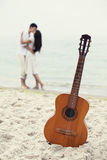 Couple kissing at the beach and guitar. Royalty Free Stock Image