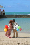 Couple Kissing on the beach. Husband and wife kissing on the beach holding balloons Stock Image