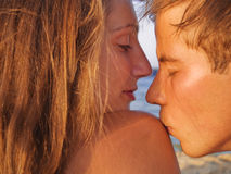 Couple kissing on the beach at sunset Stock Photos