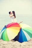 Couple kissing at the beach with umbrella Royalty Free Stock Images