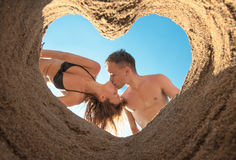 Couple Kissing on the Beach. Kissing of young couple on the beach bottom up through heart of sand Royalty Free Stock Photography