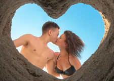 Couple Kissing on the Beach. Kissing of young couple on the beach bottom up through heart of sand Royalty Free Stock Image