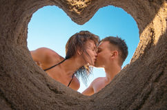 Couple Kissing on the Beach. Kissing of young couple on the beach bottom up through heart of sand Stock Images