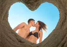 Couple Kissing on the Beach. Kissing of young couple on the beach bottom up through heart of sand Stock Image