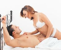 Couple kissing in bed. Middle-aged men with wife kissing and playing in bed at home Stock Image
