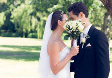 Couple kissing behind bouquet in garden Royalty Free Stock Images