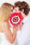 Couple kissing behind candy bunch flowers. Love. Stock Photo
