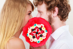 Couple kissing behind candy bunch flowers. Love. Royalty Free Stock Photography