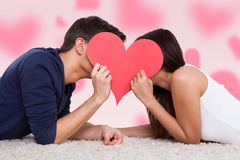 Couple Kissing Behind Heart While Lying On Fur Stock Images