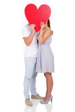 Couple kissing behind heart Royalty Free Stock Image