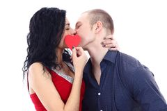 Couple kissing behind a red heart Stock Photo
