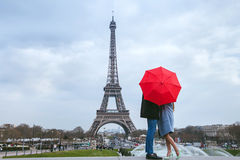 Couple kissing behind red umbrella in Paris. Honeymoon in Paris, couple kissing behind red umbrella against Eiffel tower Stock Image