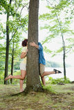 Couple kissing behind a tree Royalty Free Stock Images