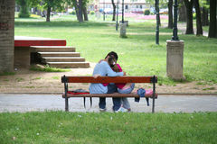 A couple kissing on a bench. A young couple in love kissing on a bench stock image