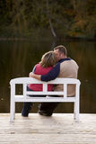 Couple kissing on a bench. At a lake in autumn stock photography