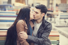 Couple kissing at the bench at alley. Stock Image