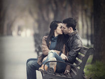 Couple kissing at the bench at alley. Couple kissing at the bench at alley stock photos