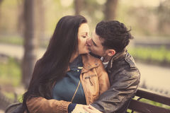 Couple kissing at the bench at alley. Royalty Free Stock Photography
