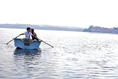 Couple kissing on boat in italian lake during vacation Stock Images