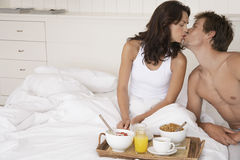 Couple Kissing By Breakfast Tray In Bed. Happy romantic couple kissing by breakfast tray in bed Stock Photos