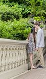 Couple kissing in Central Park. Couple holding hands with men kissing forehead of women on Bow Bridge in Central park in New York City royalty free stock image