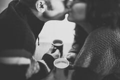 Couple kissing with coffee