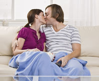 Couple kissing on couch Royalty Free Stock Images