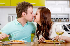 Couple kissing the dinner on the kitchen Stock Images