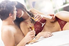 Couple kissing and drinking on the bed Stock Images