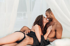 Couple kissing and embracing on white bed Royalty Free Stock Image