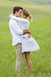 Couple kissing field Stock Images