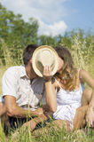 Couple kissing in the field behind hat Stock Photography