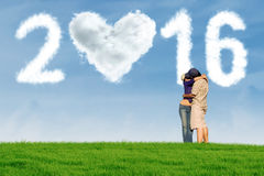 Couple kissing at field with cloud shaped numbers 2016 Stock Image