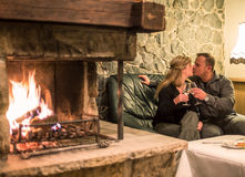 Couple kissing in fireplace room Stock Photo
