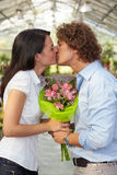 Couple kissing in flower nursery Royalty Free Stock Images