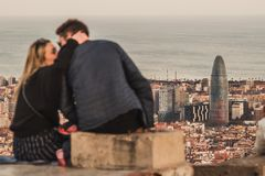 A couple is kissing in front of the views of Barcelona, Spain. It is sunset time stock image