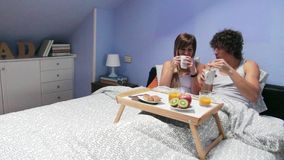 Couple kissing and having breakfast in bed served stock video