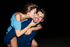 Couple kissing and having fun on the beach at night. Happy young couple kissing and having fun on the beach at night royalty free stock image