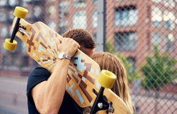 Couple kissing and hiding. Behind skateboard, big city couple Stock Photography