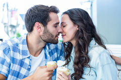 Couple kissing while holding cupcakes Royalty Free Stock Image