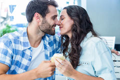 Couple kissing while holding cupcakes Stock Photography