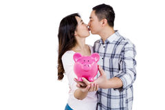 Couple kissing while holding piggy bank Royalty Free Stock Photos