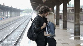 Couple kissing and hugging in train station on rainy day before separation stock video footage