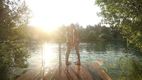 Couple kissing and jumping into water from river dock stock video